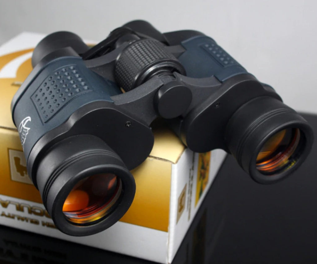 black night vision zoom binoculars sitting on top of a box