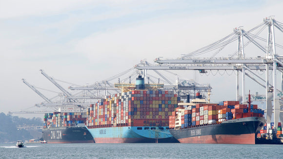 What is a transshipment and how does it affect transit times?
