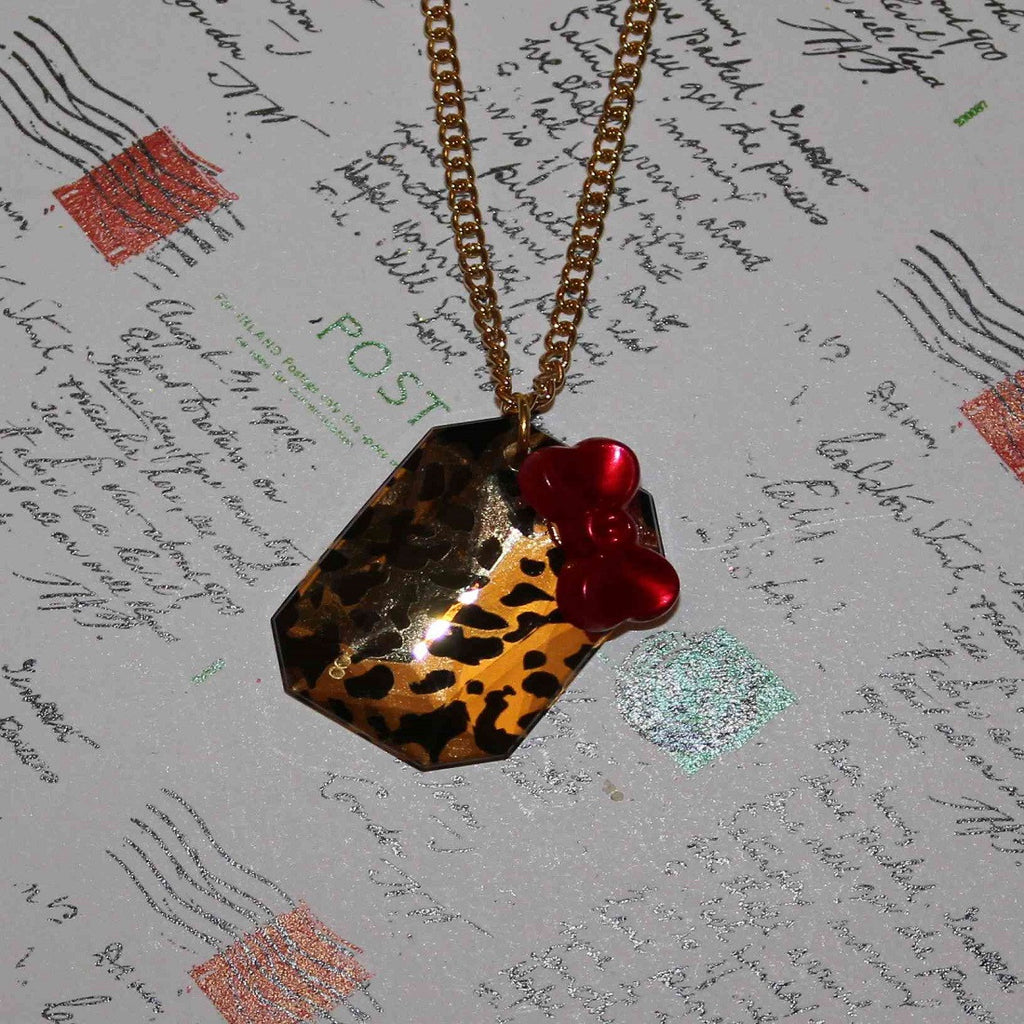 leopard print tile with red bow necklace