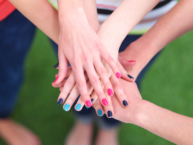 manicurist team bonding with hands stacked on top of each other