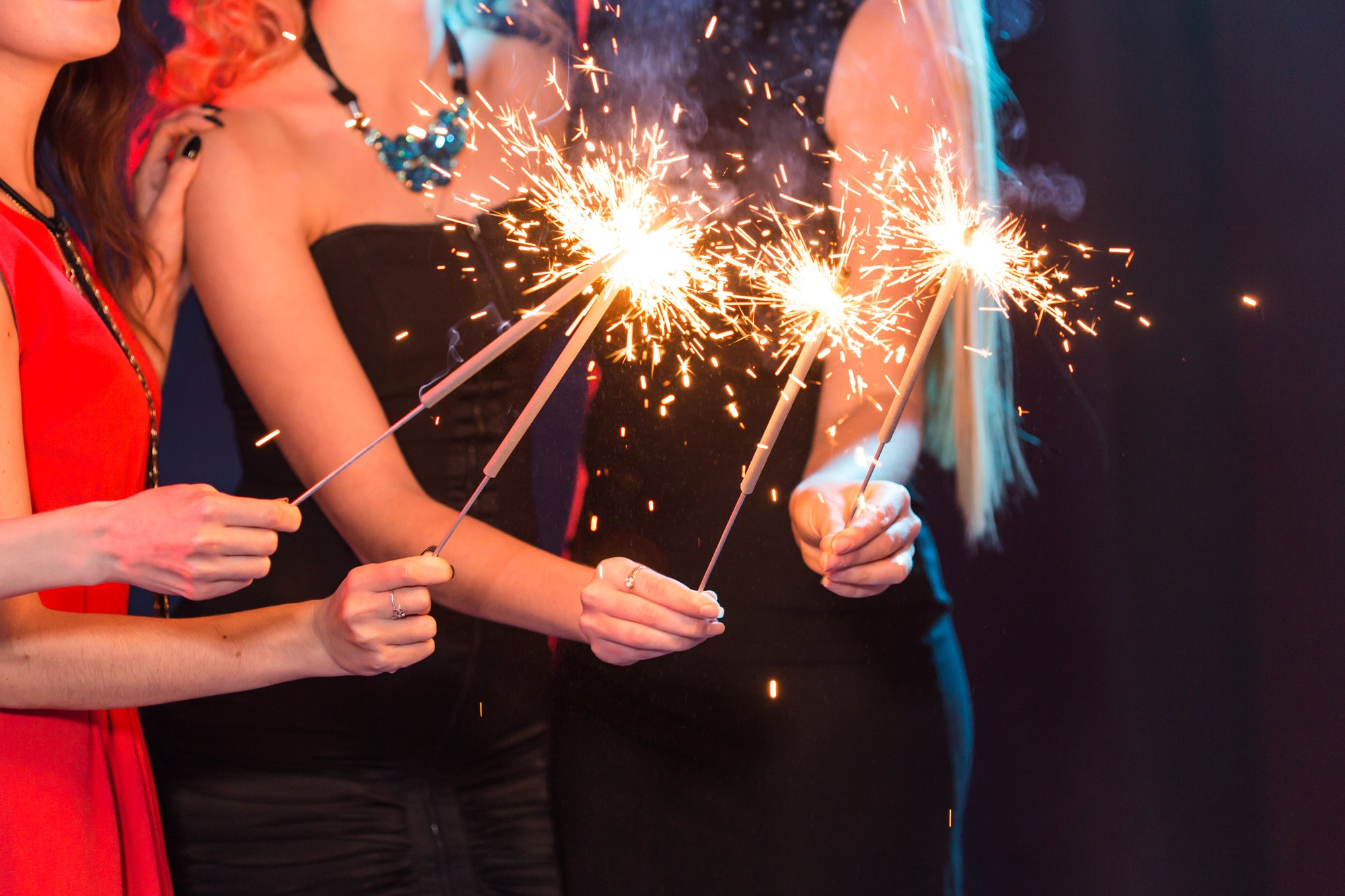 group of ladies enjoying night party events lighting sparklers