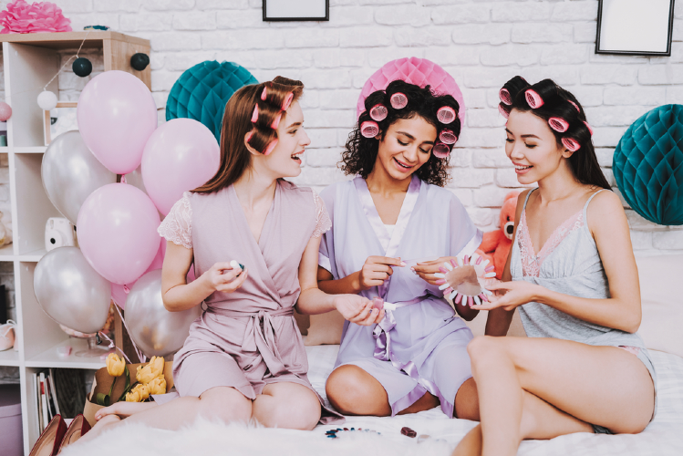 bridal party for hen's night party event of three girls in their room choosing nail colors