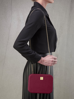 Atelier Verdi pink leather clutch bag worn over the shoulder by model