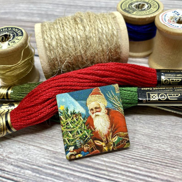 Santa and a Reindeer Decorating a Tree Needle Minder