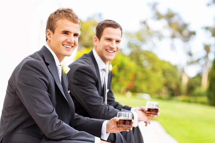 A groom and his best man drinking whiskey before the ceremony