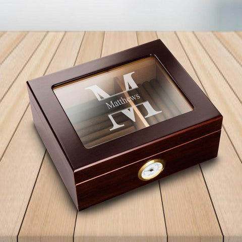 A Mahogany personalized humidor filled with cigars that has a glass top that says matthews