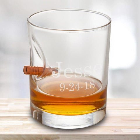A personalized whiskey glass that says Jesse with a bullet lodged into the side