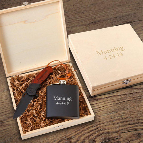 A wooden knife box with a personalized pocket knife and drinking flask inside