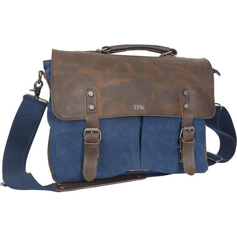 A blue travel duffle bag with a brown leather flap over the top with the initials TPK on the top