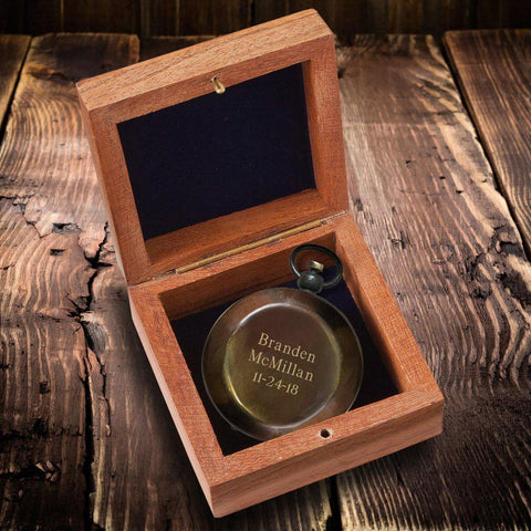 A bronze colored compass sitting in a brown wooden box