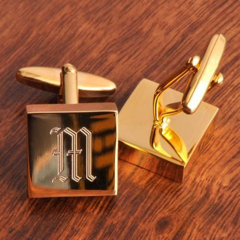 Two high-brass polished cufflinks sitting on a brown table with the letter M in the middle