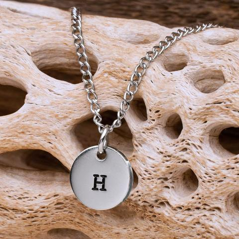 A silver medallion with a black H hanging on a silver chain