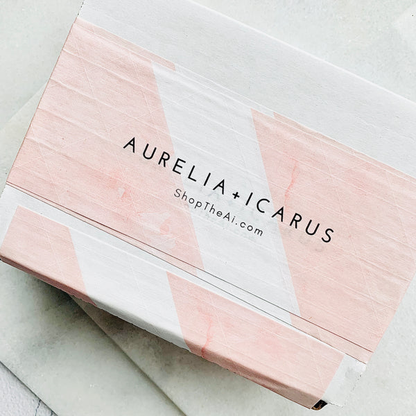Photo of a chic, Aurelia + Icarus Branded Rose and White Shipping Box against a white neutral backdrop.