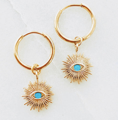 Dainty, small gold evil eye sunburst pendants with tiny turquoise 'eyes' on small minimalist hoop earrings.