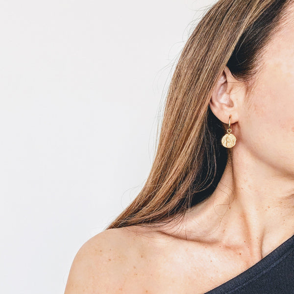 Image of model in an alternate pose wearing a pair of bee gold coin mini hoop earrings