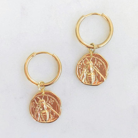 A pair of gold bee coin small hoop earrings against a neutral background.