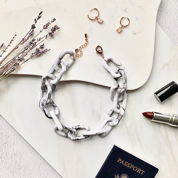 Stylish flat lay photo of the Chunky Grey and White Chain Necklace against a white marbled background, accessorized with flowers, small hoop earrings, lipstick and a passport in the background.