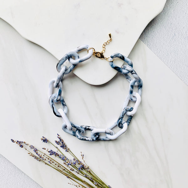 Stylish photo of the Chunky Grey and White Chain Necklace against a marble background with a some lavender flowers.