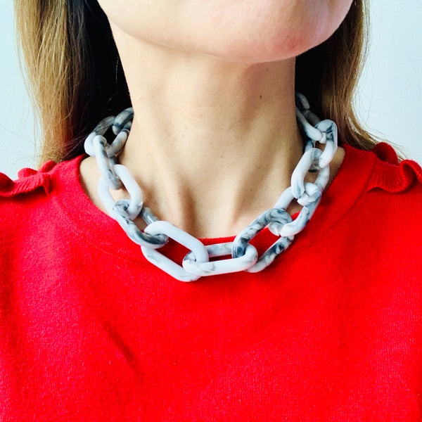 Close up image of model wearing a red top and the Chunky Grey and White Marbled Chain Necklace by Aurelia + Icarus Jewelry.