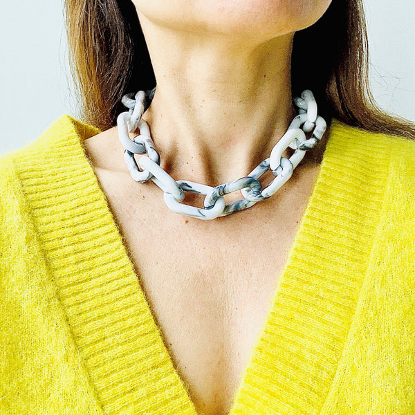 Close up of model in a v neck yellow top wearing the Chunky Grey and White Marbled Chain Necklace by Aurelia + Icarus Eco Slow Jewelry