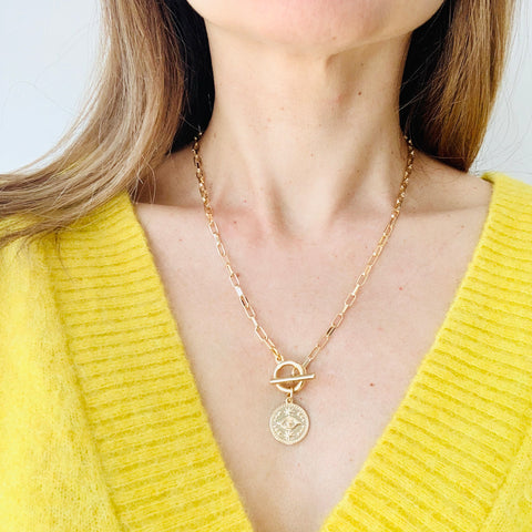 Model wearing Evil Eye Gold Coin Toggle Chain Necklace with a v-neck top.