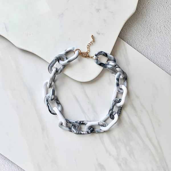 Stylish flat lay photo of Chunky Grey and White Marbled Chain Carabiner Necklace against a marble background by Aurelia + Icarus Eco Friendly Slow Jewelry