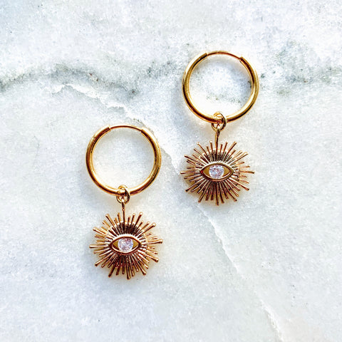 Dainty, small gold evil eye sunburst pendants with tiny cubic zirconia 'eyes' on small minimalist hoop earrings.
