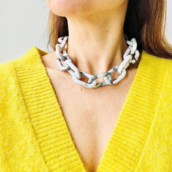Close up of model turning her head in a v neck yellow top wearing the Chunky Grey and White Marbled Chain Necklace by Aurelia + Icarus Eco Slow Jewelry