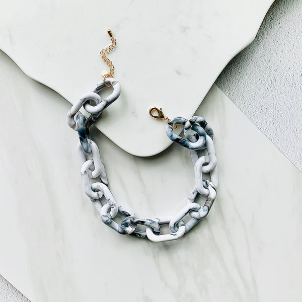 Stylish photo of the Chunky Grey and White Chain Necklace casually laid out unclasped against a marble background.