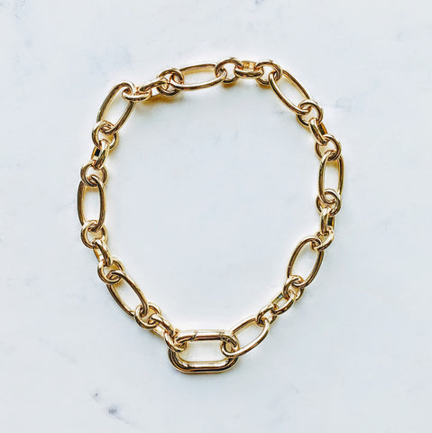 Carabiner Gold Chain Necklace displayed on a marble background.