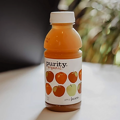 Purity Organic Apple Juice sitting on counter with plants in background
