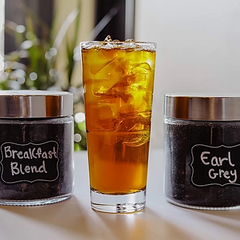 glass of iced black tea with jars of loose leaf teas behind