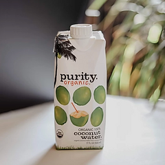 Purity Organic Coconut Water sitting on counter with plants in background
