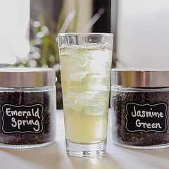 glass of iced green tea with jars of loose leaf teas behind