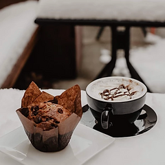 muffin on dish next to a hot mocha