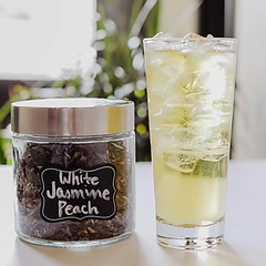 glass of iced white tea with jars of loose leaf teas behind