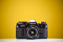 Load image into Gallery viewer, Canon AE-1 Program Black 35mm Film Camera with Canon FD 50mm f/1.8 Lens and Data Back