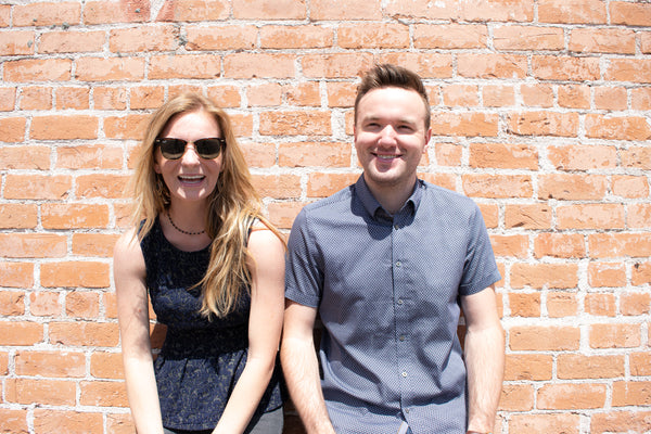 2 people standing in front of a brick wall