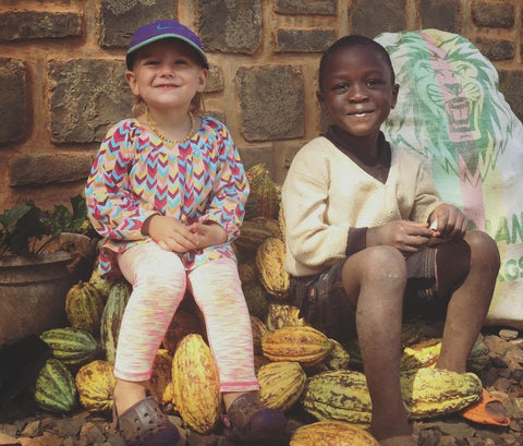 two children sitting on cacao pods
