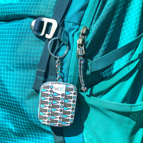 Keychain with a reusable silicone straw in it attached to a blue backpack