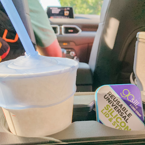 A paper cup with a stretchy silicone lid and a silucone straw in it. The cup sits in a car with the driver on the background.