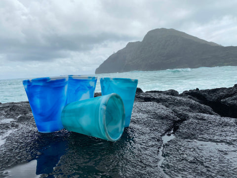 Four Gosili Silicone Ocean Cups sitting on a rock with the ocean as background
