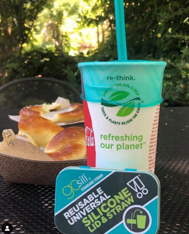 A paper cup with a silicone lid and straw sitting at a table in a patio or park