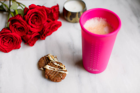 A reusable silicone cup filled with a vegan pumpkin latte. Next to it there are two cookies, a candle, and a bouquet of roses