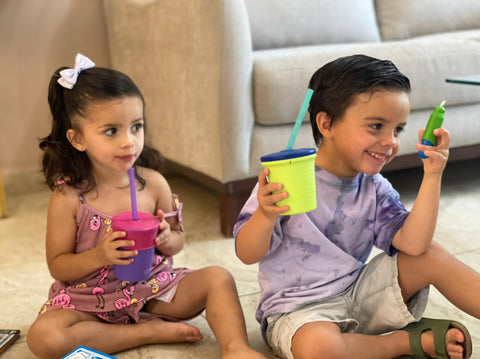 Two kids sitting on the floor holding silicone reusable cups with straws