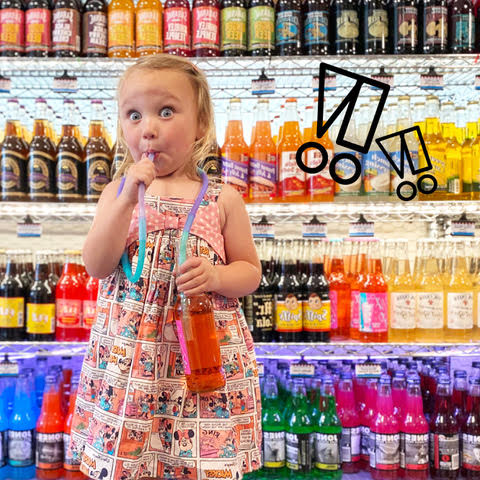Kid standing in front of the drink aisle sipping on a drink using silicone straws attached to each other