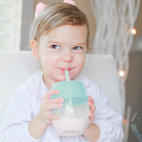 Toddles holding a glass with a stretchy silicone lid and straw