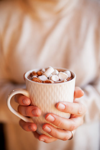 A set of woman's hands is holding a white cup with hot chocolate with marshmallows in it.