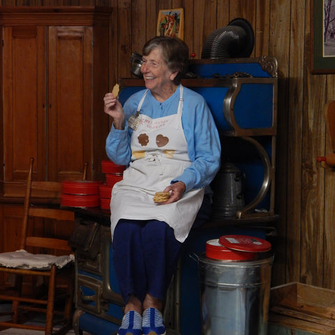 Mrs. Hanes' posing with cookies next to an antique wood stove.