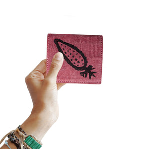 A woman holding a block printed pink cardholder wallet